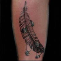 Great gray-ink eagle feather with little green rocks tattoo