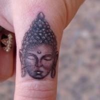 Tatuaje en el dedo, cara de buda, tinta gris