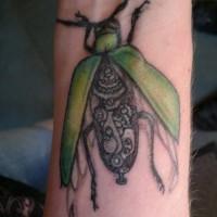 Green biomechanical bug tattoo on wrist