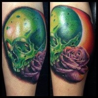 Green colored leg tattoo of big human skull and violet rose