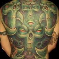 Tatuaggio terribile sulla schiena le facce verde demoniche con gli occhi rossi
