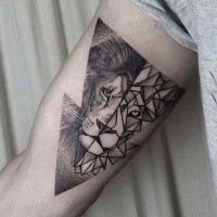 Half geometrical half dot style black ink biceps tattoo of lion head