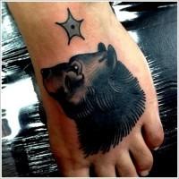 testa di orso nero con stella tatuaggio sul piede