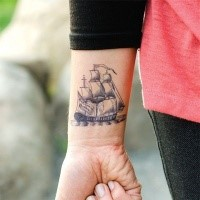 Homemade style black ink wrist tattoo of cool sailing ship