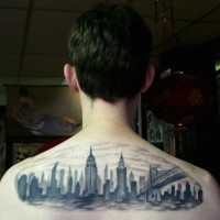 Homemade watercolor like black ink upper back tattoo of nigh city sights