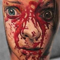 film orrore faccia di ragazza insanguinosa tatuaggio su gamba