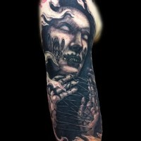 Horror movie like black ink horrifying witch tattoo on upper arm