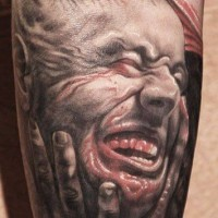 Horror movie like detailed and colored bloody monster face tattoo on leg