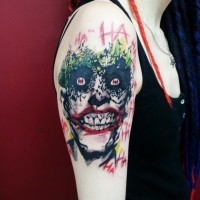 Horror movie like smiling Joker tattoo on shoulder with lettering