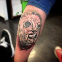 Horror movie masked monster face tattoo on leg