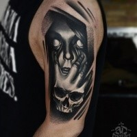 Horror style black ink shoulder tattoo of creepy woman face with hand skull