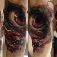 Horror style creepy looking biceps tattoo of bloody eye with knife