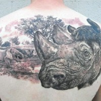 Huge detailed colored rhino head tattoo on upper back combined with elephant in wild life