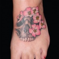 Human skull fragment with pale pink tender flowers foot in horror style