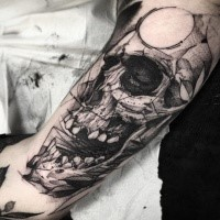 Human skull with open mouth and circle on forehead tattoo in engraving style