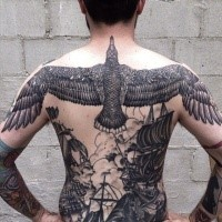 Illustrative style black ink whole back tattoo of large bird with ships