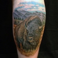 Illustrative style colored leg tattoo of wild bull with mountains