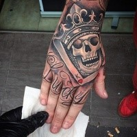 Illustrative style colored skull king with crown tattoo on hand with lettering