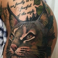 Illustrative style colored thigh tattoo of caracal with lettering and feather