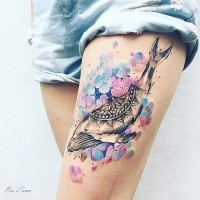 Illustrative style colored thigh tattoo of whale with flowers