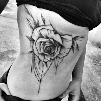 Impressive big black ink rose tattoo painted by Inez Janiak on side