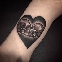 Impressive heart shaped tattoo stylized with kissing skeleton couple