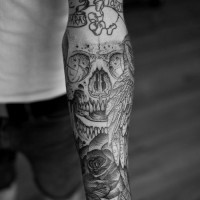 Interesting-designed gray-ink skull with wing and rose tattoo sleeve on forearm