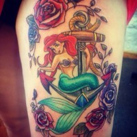 Interesting nautical themed colorful tattoo on thigh with cartoon mermaid and anchor