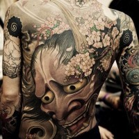 Large demon mask tattoo on back in asian style