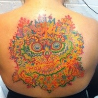 Large multicolored upper back tattoo of flowers and cat like face