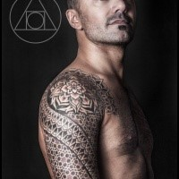Large shoulder tattoo of Polynesian style ornaments
