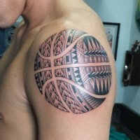 Large unusual looking basketball tattoo on shoulder stylized with Polynesian ornaments