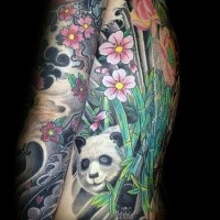 Lifelike colored tattoo of panda bear with flowers and bamboo