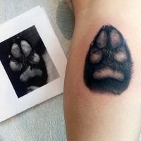 Lifelike very detailed tattoo of small dog paw