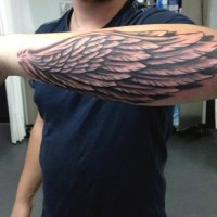 Little black ink detailed wing tattoo on arm