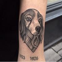 Kleines schwarzes Hundeporträt Tattoo am Arm mit Schriftzug