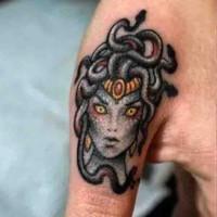 Little cartoon like colored Medusa head tattoo on finger