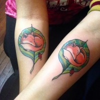 Little colored identical sleeping fox on leaf couple tattoo on forearm combined with ladybug