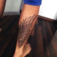Little realistic looking black ink wing tattoo on leg