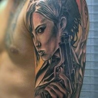 Magnificent angel woman with pistol tattoo on shoulder
