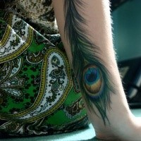 Magnificent peacock feather naturally colored forearm length tattoo in realism style