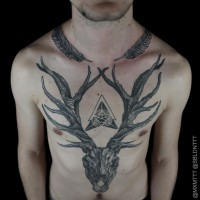 Massive black and white 3D like deer skull tattoo on chest stylized with mystical symbol and feather