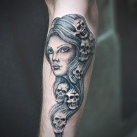 Medium size simple painted and colored arm tattoo of woman stylized with human skulls