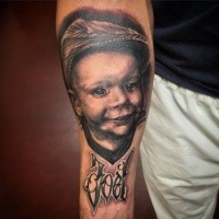 Memorial style black and gray style forearm tattoo of boy portrait and lettering