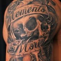 Memorial style black ink shoulder tattoo of human skull and lettering