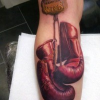Memorial style colored boxer gloves with lettering tattoo on arm