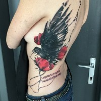 Memorial style painted colored crow with flowers and lettering tattoo on waist and back