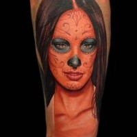 Mexican style colored arm tattoo of woman face with ornaments