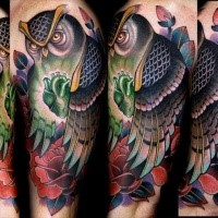 Modern style colored shoulder tattoo of big owl with flowers and glowing heart