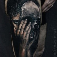 Modern style colored thigh tattoo painted by Eliot Kohek thigh of woman with skull shaped mask